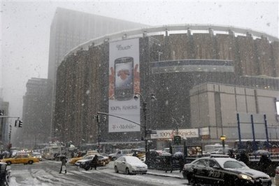 Pedestrians and traffic navigate the intersection near Madison Square Garden as snow falls in  New York. (AP Photo/Frank Franklin II)