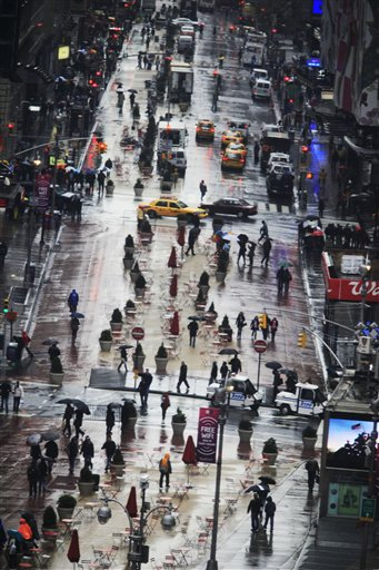 Pedestrians make their way in New York's Times Square in the rain, Monday, March 29, 2010, in New York. (AP Photo/Mary Altaffer)