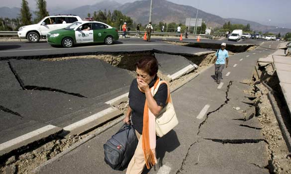 A woman walks by a destroyed road in Santiago, Chile. (Ian Salas/EPA)