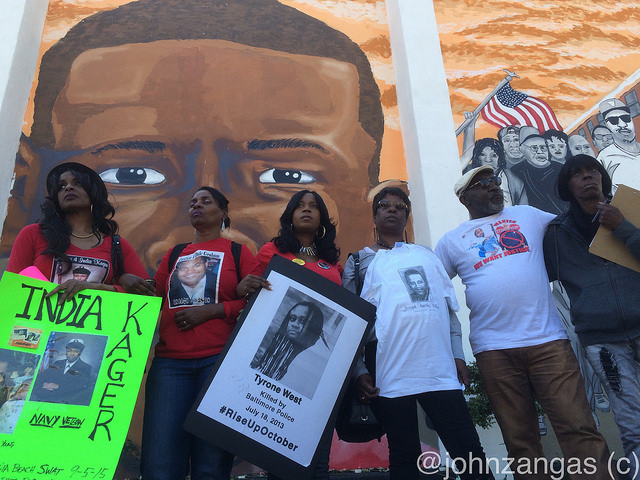 Families of those killed by police stand in front of mural of police victim Freddie Gray./Photo by John Zangas